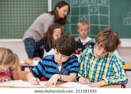 Young children in class writing notes in their school notebooks while sitting together at a desk with a female teacher busy in the background at the blackboard - stock photo