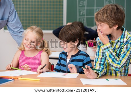 Young children laughing at a classmate as they look at something funny that a pretty little blond girl has written in her school notebook