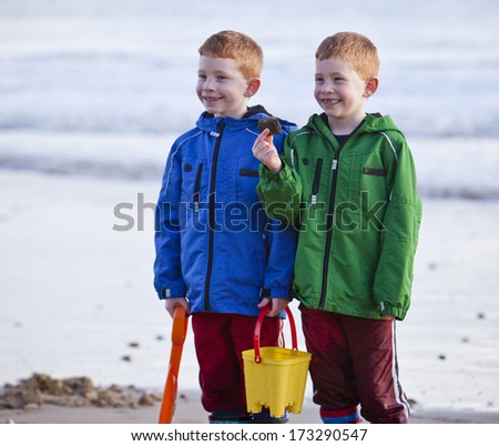 Young children playing on a beach in winter