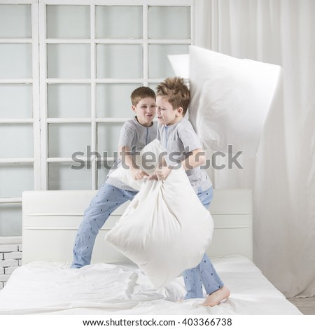 Young children playing on the bed. Pillow fight
