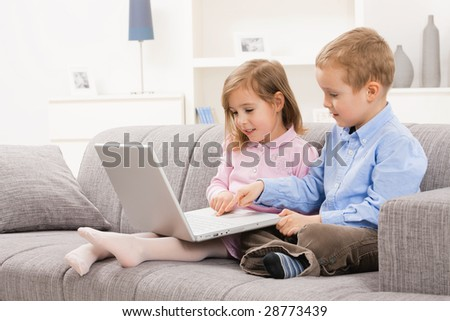 Young children sitting on couch at home, browsing internet on laptop computer, looking at screen.