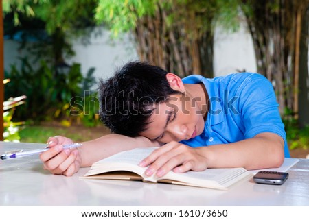 Young Chinese Asian student is bored at home with difficult homework assignment for school next day, he has fallen asleep - stock photo