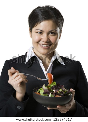 Young chinese businesswoman eating salad
