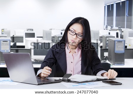 Young chinese businesswoman working in the office while making a plan on notebook - stock photo