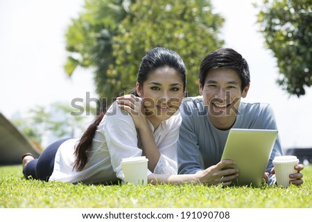 Young Chinese couple using tablet PC in urban city park.