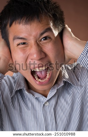 Young Chinese frank businessman yelling, closeup portrait in studio. - stock photo