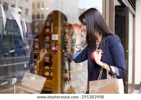 young chinese girl looking in a shop window - stock photo