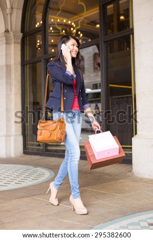 young chinese girl talking on the phone - stock photo