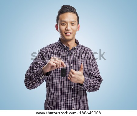 young chinese man holding an electronic car key - stock photo