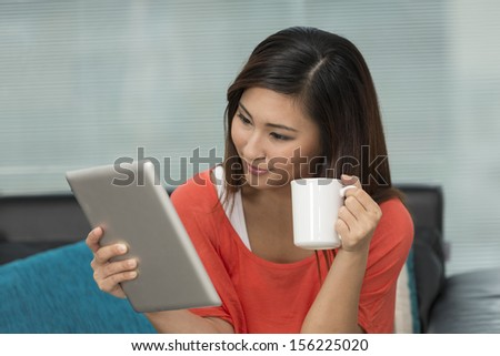 Young Chinese woman at home relaxing in her lounge reading a digital tablet PC.