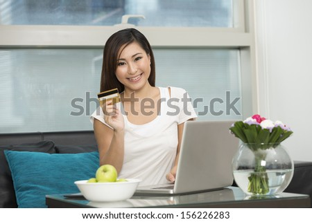 Young Chinese woman at home relaxing on Sofa and Shopping Online