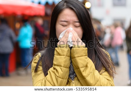 Young Chinese woman blowing her nose on a cold winter night outdoors as she attends a Christmas market viewed behind the branch of a natural evergreen Xmas tree in a concept of health and seasonal flu