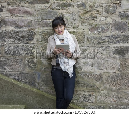 Young Chinese woman using a tablet pc outside and leaning against a stone wall.