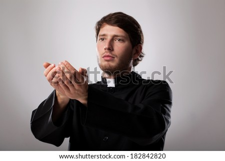Young christian faithful priest is preaching a sermon - stock photo