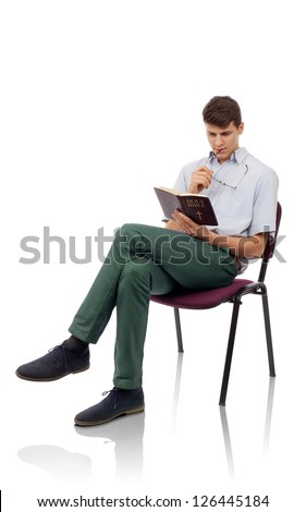 Young christian man sitting and reading Holy Bible - stock photo