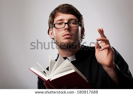 Young christian priest in glasses with Holly Bible - stock photo
