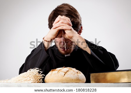 Young christian priest is praying and blessing - stock photo