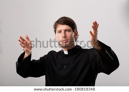 Young christian priest is preaching a sermon - stock photo