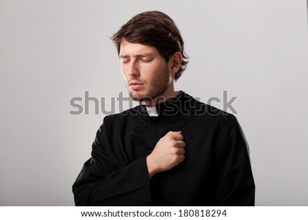 Young christian priest is regretting for sins - stock photo
