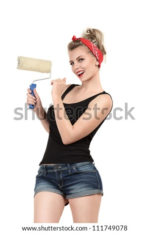 Young classic pin-up woman painting wall with paint roller - stock photo