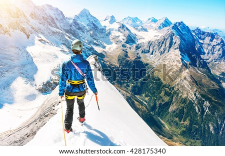 Young climber reaching the summit, Nepal Himalayas - stock photo
