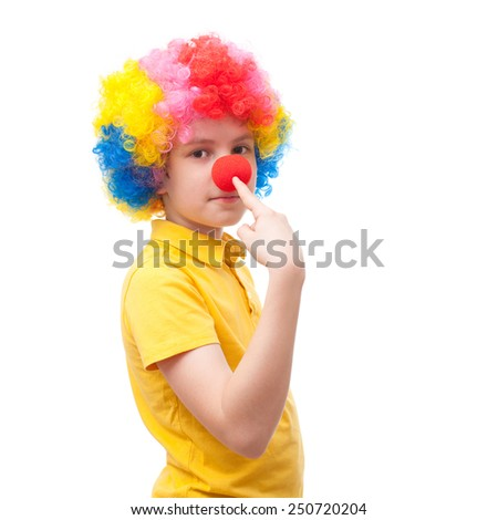 Young clown points to his own red nose  - stock photo