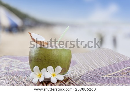 young coconut fresh drink with blur beach background