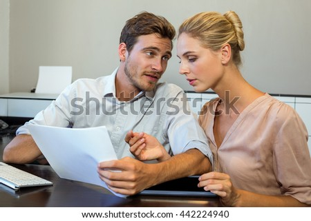Young colleagues discussing by desk in office - stock photo
