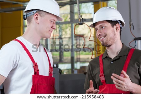 Young colleagues from factory discussing during work