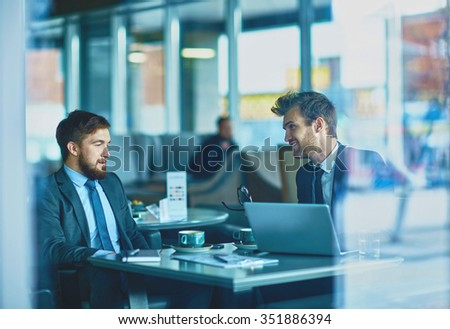 Young colleagues talking at meeting in cafe - stock photo