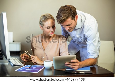 Young colleagues using digital tablet at desk in office - stock photo