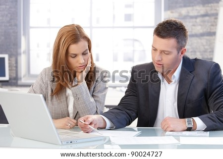 Young colleagues working in bright office, having laptop.?