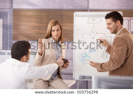 Young colleagues working together over whiteboard, smiling. - stock photo