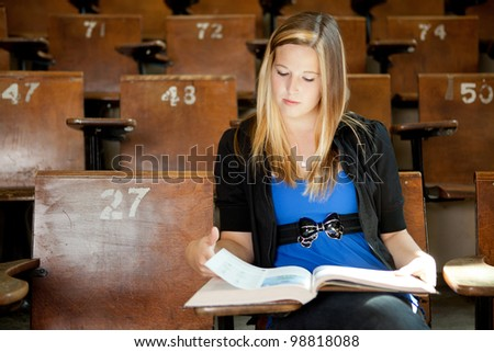 Young college girl looking at text book in lecture hall - stock photo
