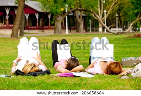 young college or high school student a break from learning on the grass in the park with his feet cocked in the air/young college or high school student - stock photo