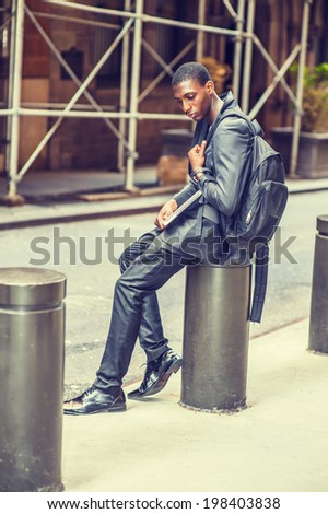Young College Student. Carrying a bag, holding a laptop computer, a young handsome black guy is sitting on street, looking down, sad.  - stock photo