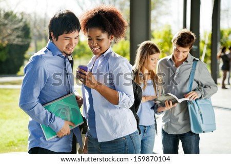 Young college students reading text message on mobilephone in campus - stock photo