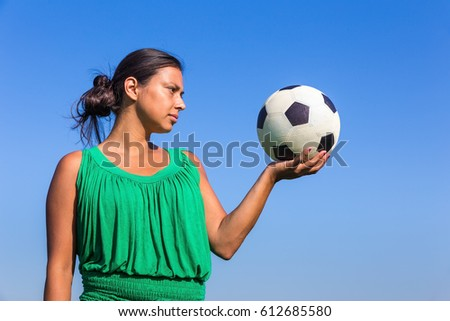 Young colombian woman holding football on hand with blue sky
