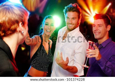 Young companionship having fun in discotheque.