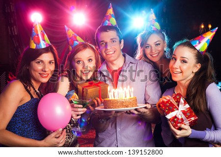 young company holds a cake with candles on birthday - stock photo
