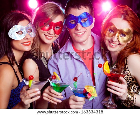 young company in mask celebrates holiday with a cocktail in hand - stock photo