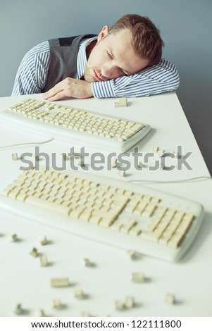 Young computer geek with beard in suit lying on the table with disassembled keyboards - stock photo