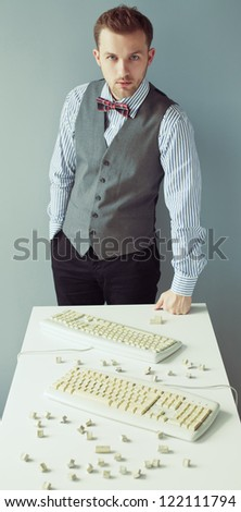 Young computer geek with beard in suit near the table with disassembled keyboards - stock photo