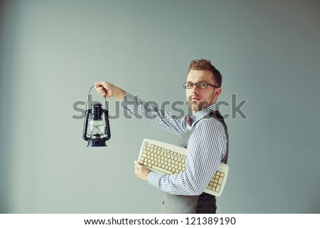 Young computer man in suit and eyeglasses holds keyboard and candlestick - stock photo