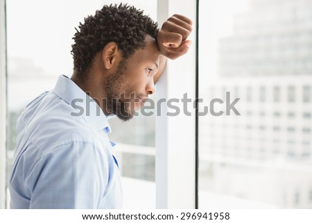 Young concentrated businessman looking out of the window and leaning against it in the office - stock photo