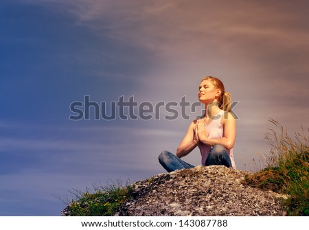 Young concentrated female meditating on hill at the sunset. - stock photo