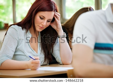 Young concentration student girl doing test in class - stock photo