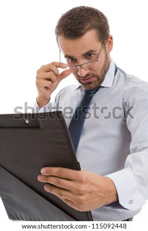 Young concerned accountant looking over eyeglasses at black folder with documents, over white background. - stock photo