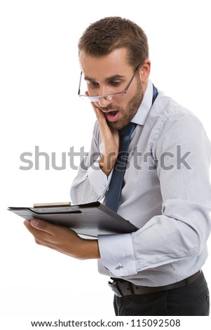 Young concerned businessman with hand on his cheek looking over eyeglasses at black folder with documents, over white background. - stock photo