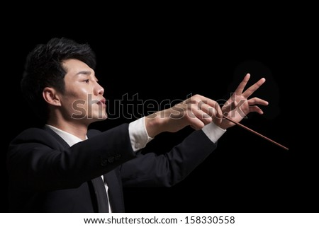 Young conductor with baton raised